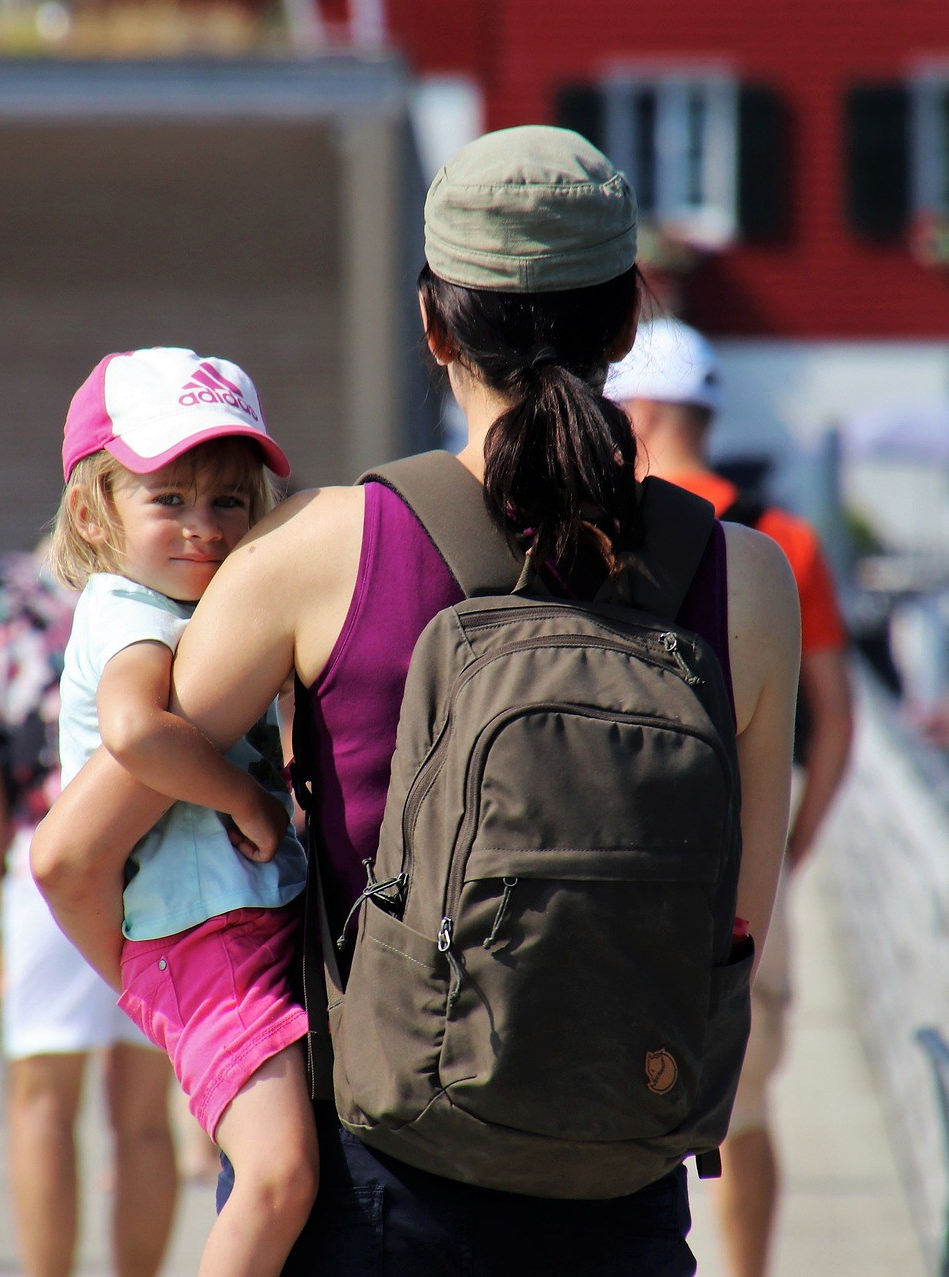 Mom wearing a small packpack and carrying her little girl