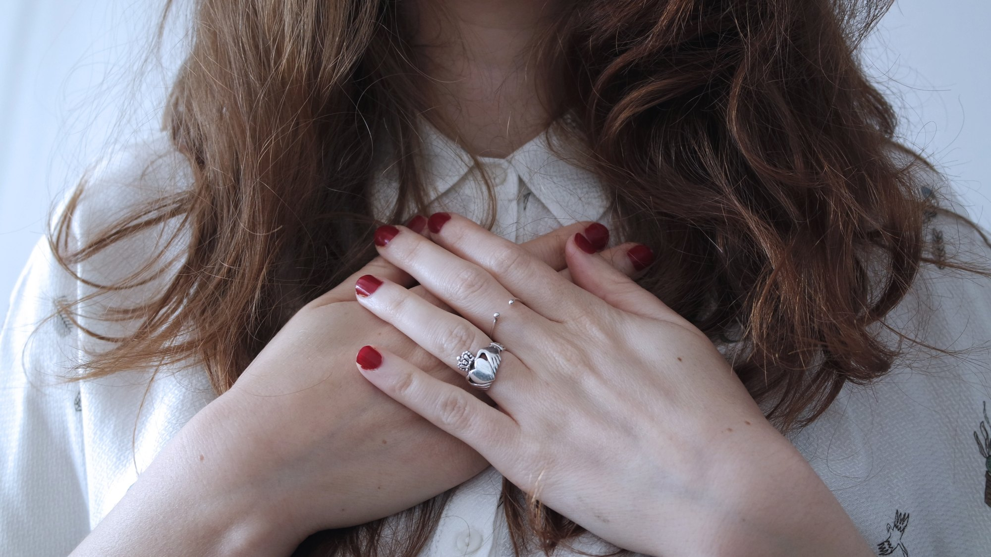 Woman holding her hands over her heart