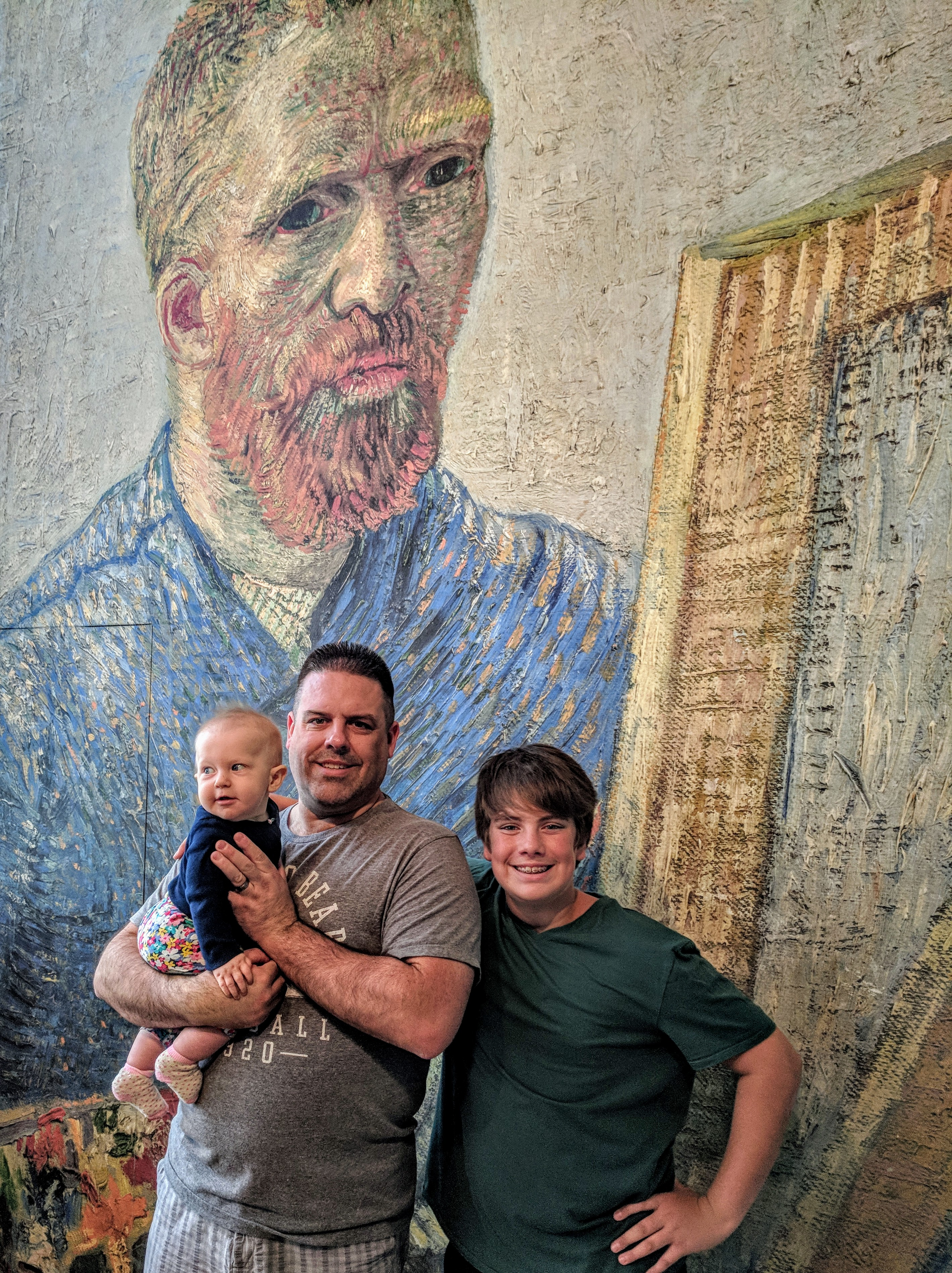 Family posing in front of Vincent Van Gogh portrait at Vincent Van Gogh Musuem