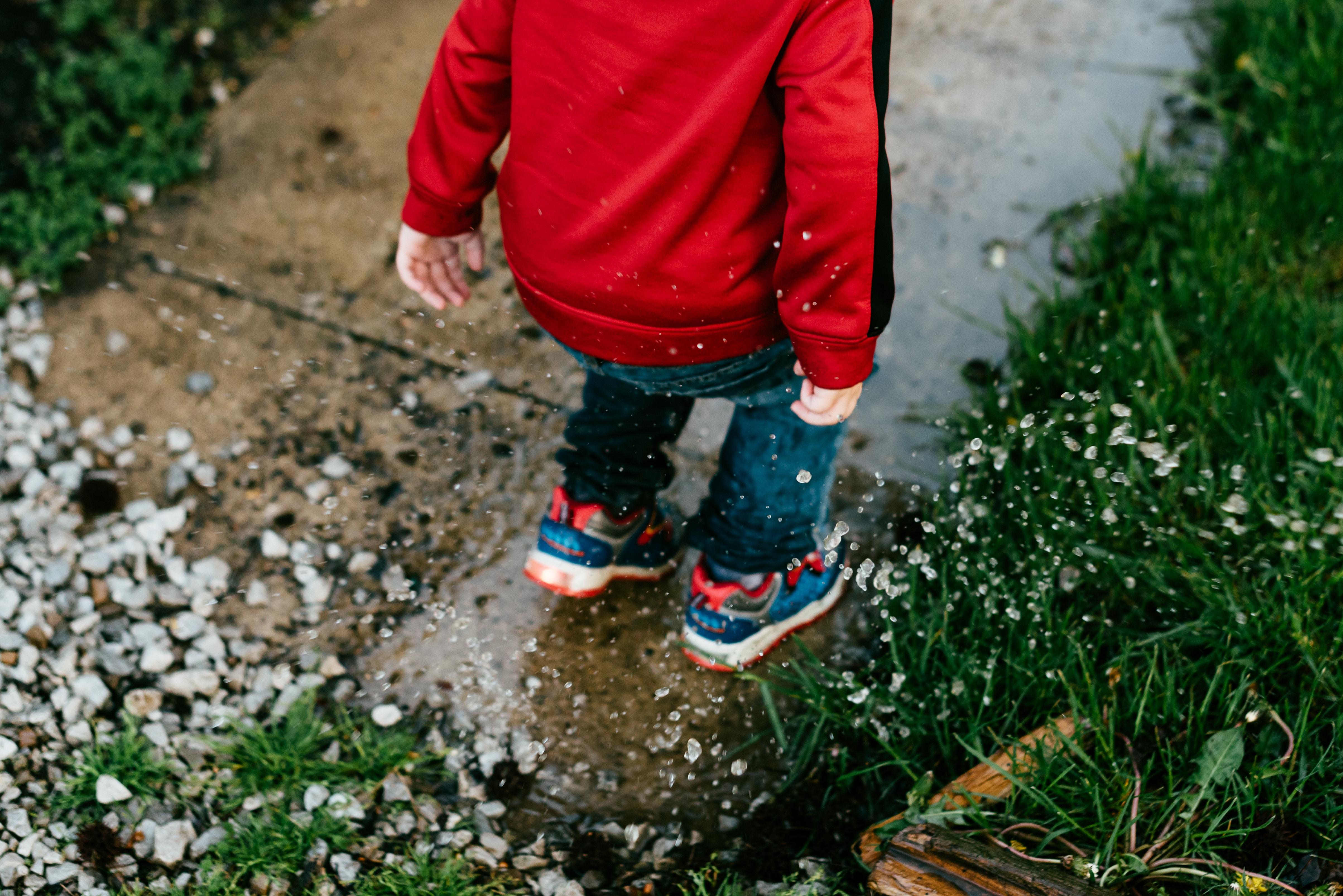 kid splashing in puddles