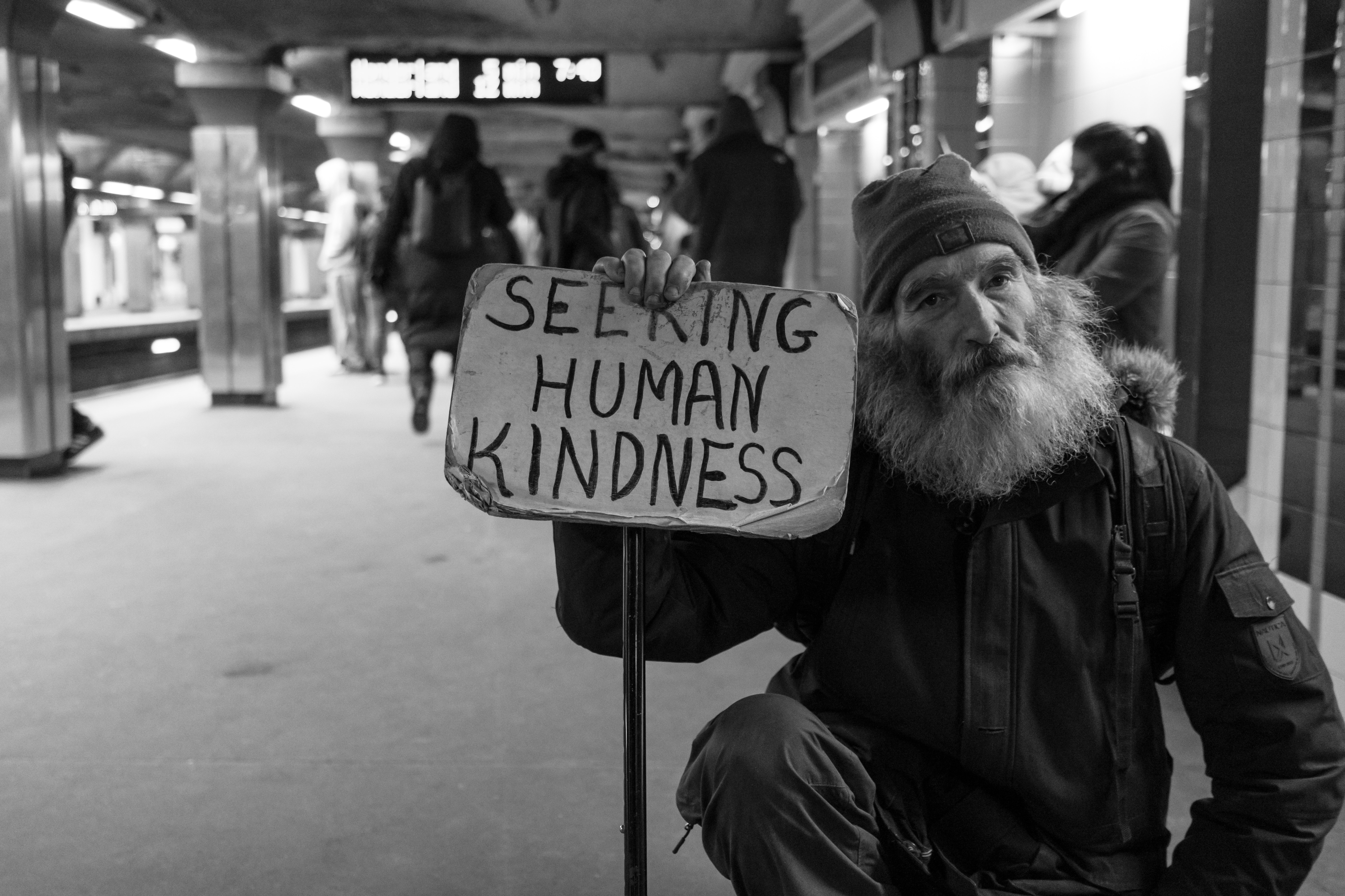 homeless man with a sign saying seeking human kindness