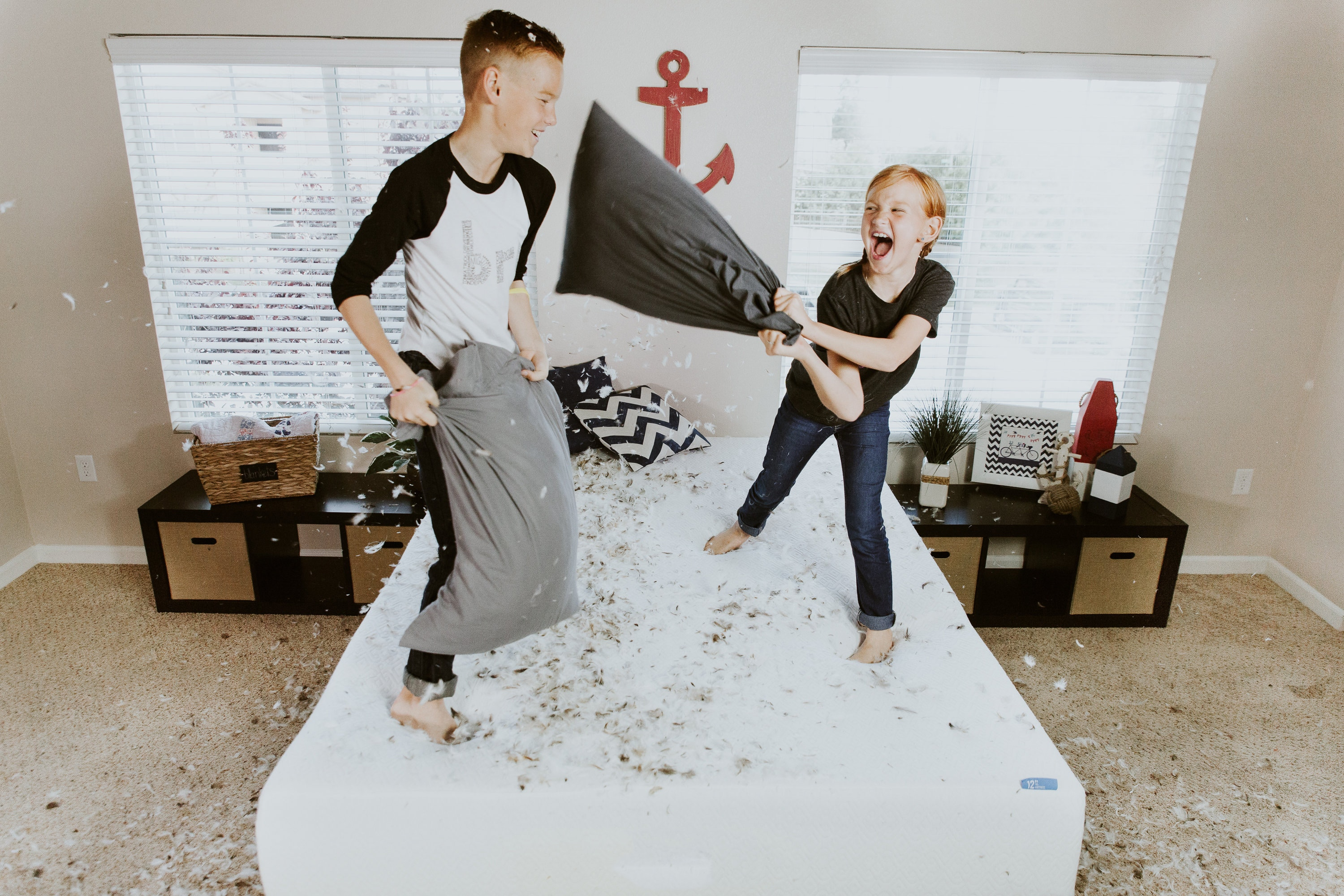 Little boy and girl having a pillow fight with feathers flying all over the floor.