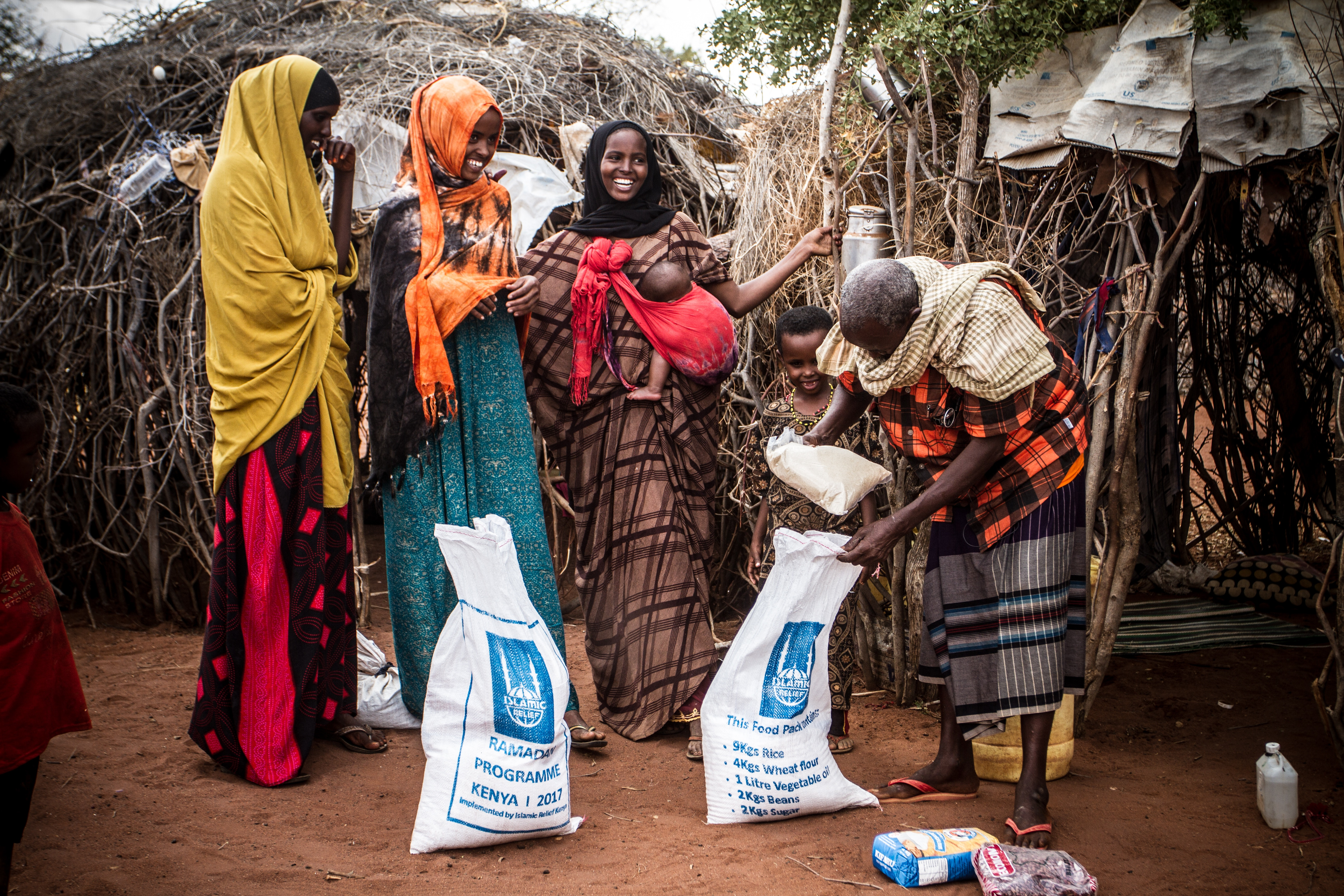 A group of Kenyan women standing in front of huts receiving two bags of rice.