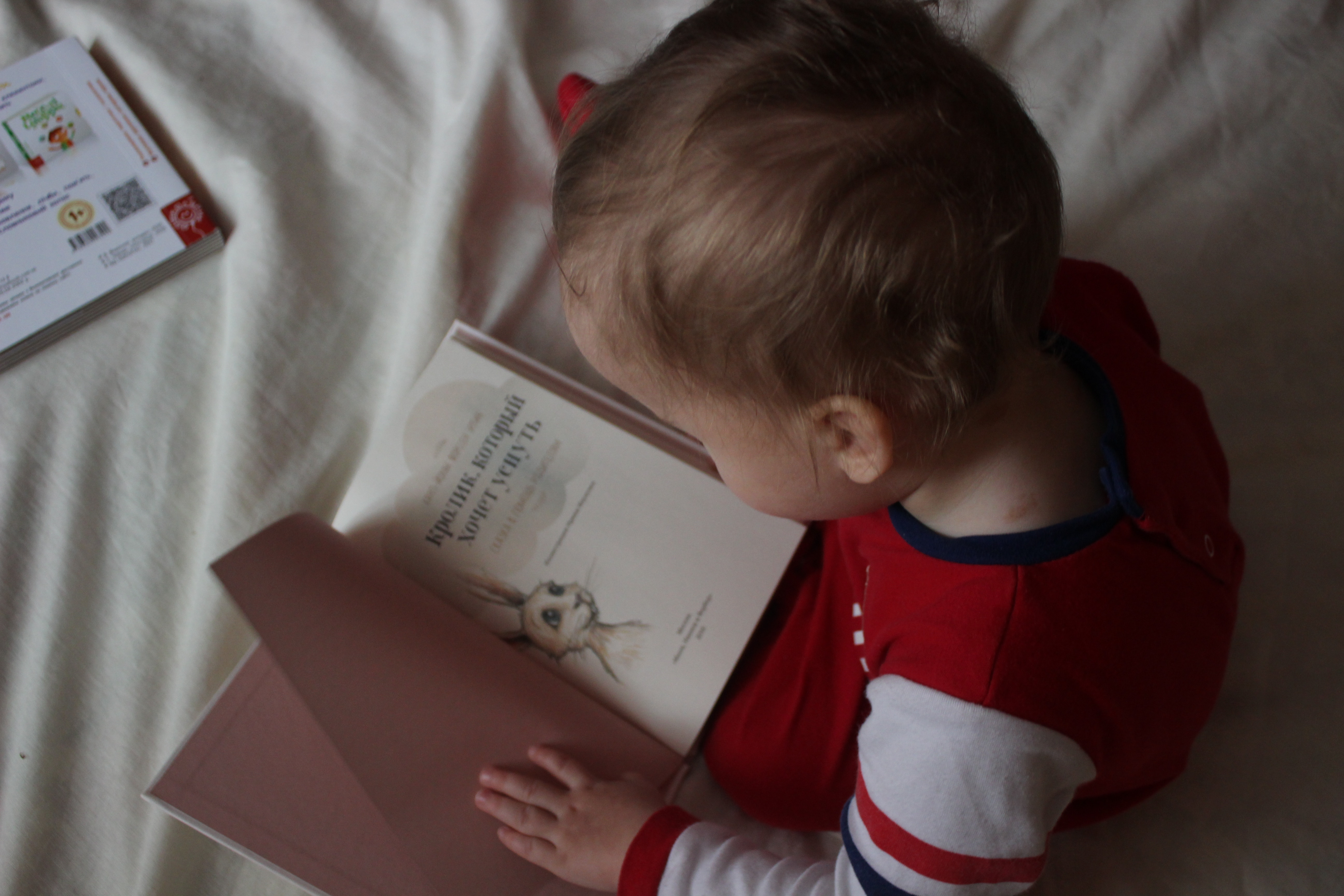 Little baby sitting on a bed reading a Russian book.