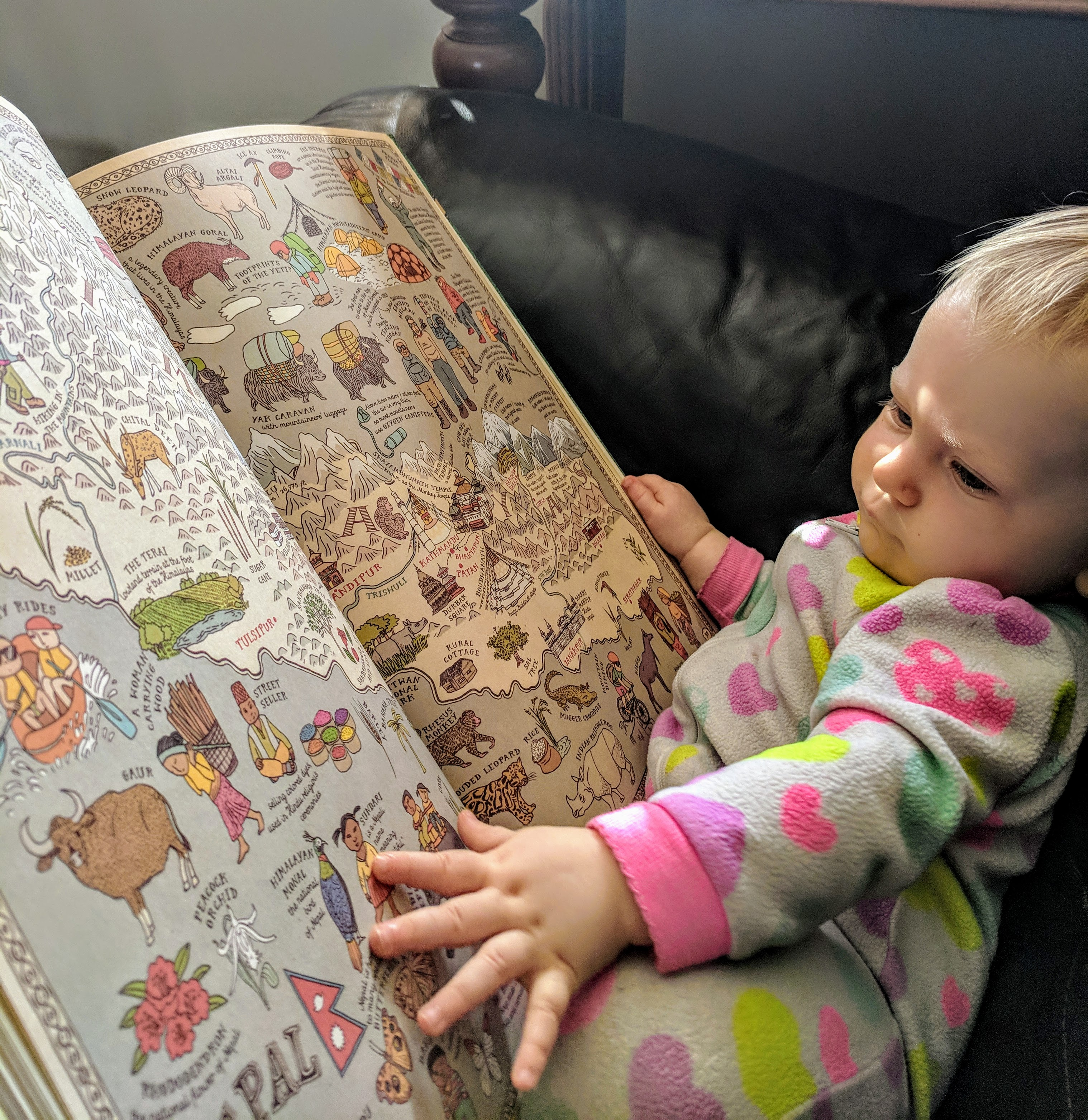 Little girl looking through a map book while sitting on the couch.