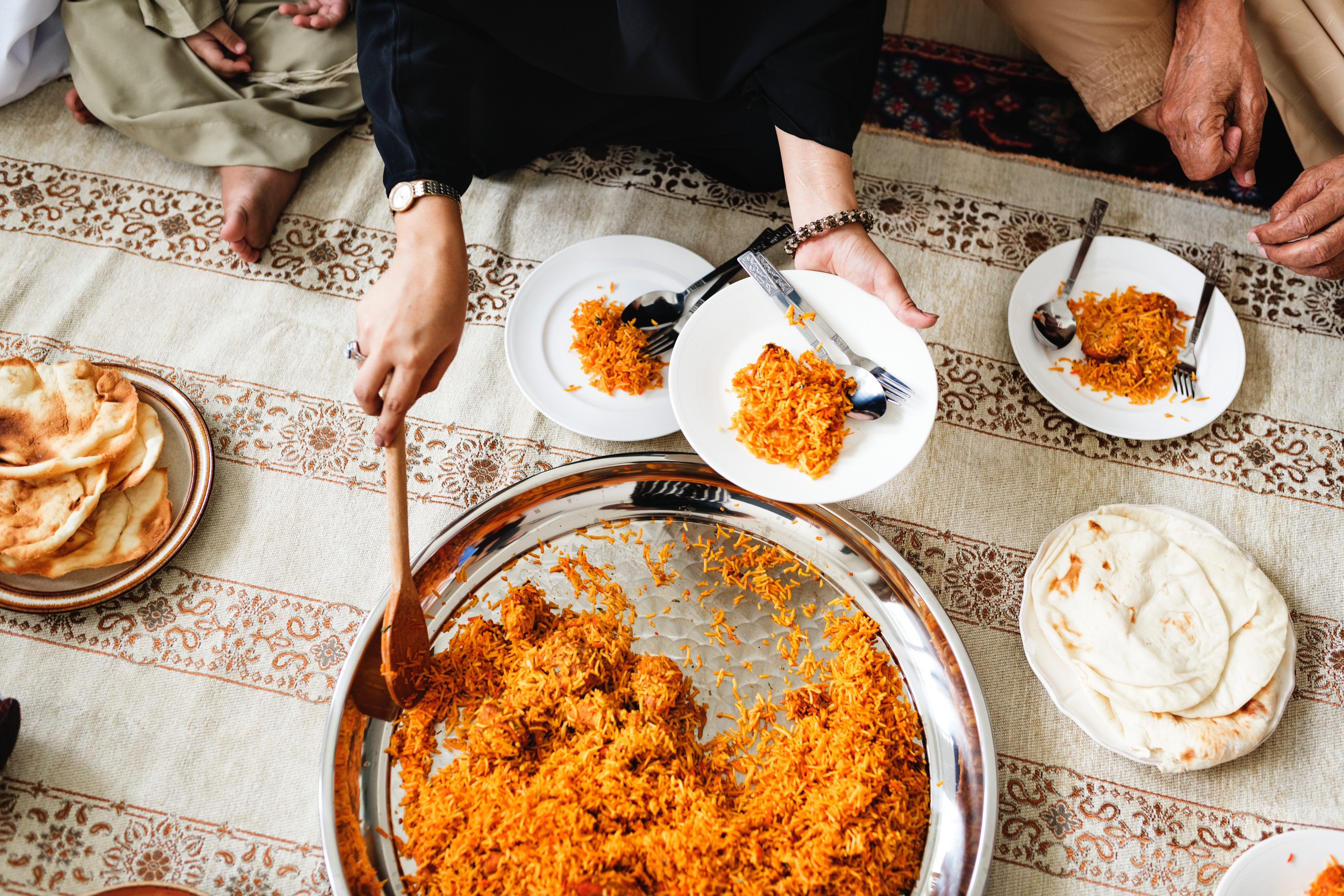 Woman serving rice onto a plate while sitting on a blanket on the floor.