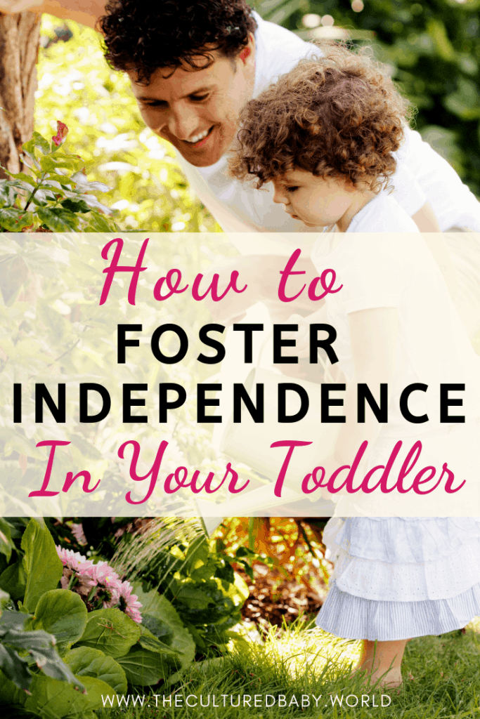 A toddler watering flowers with her father standing next to her | fostering independence in your toddler