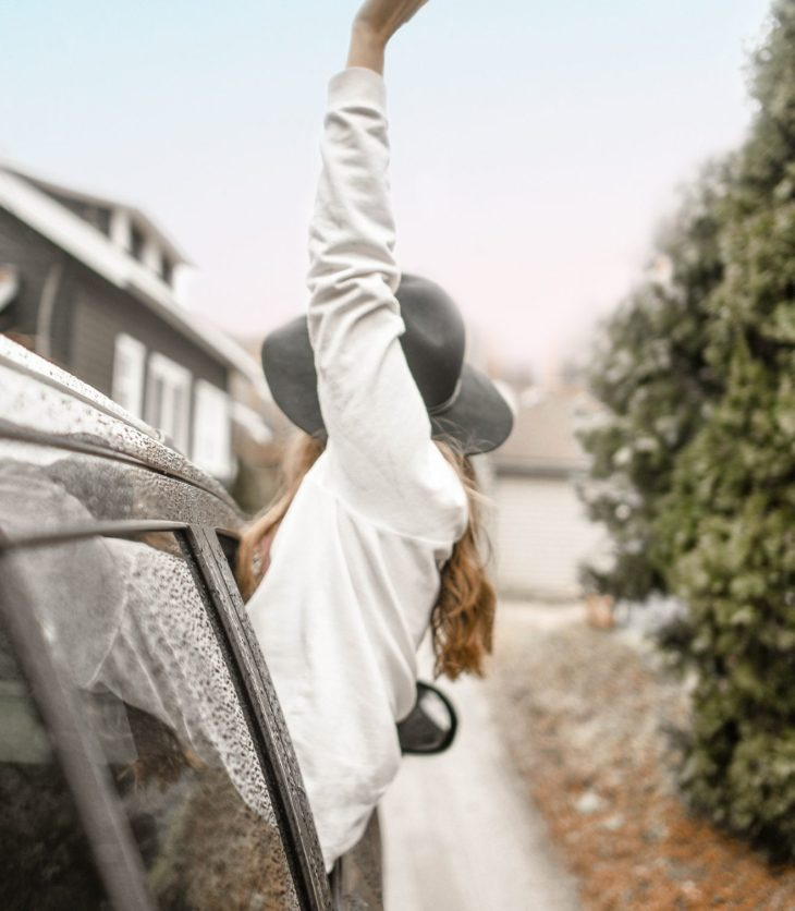 woman hanging out of her car in the rain