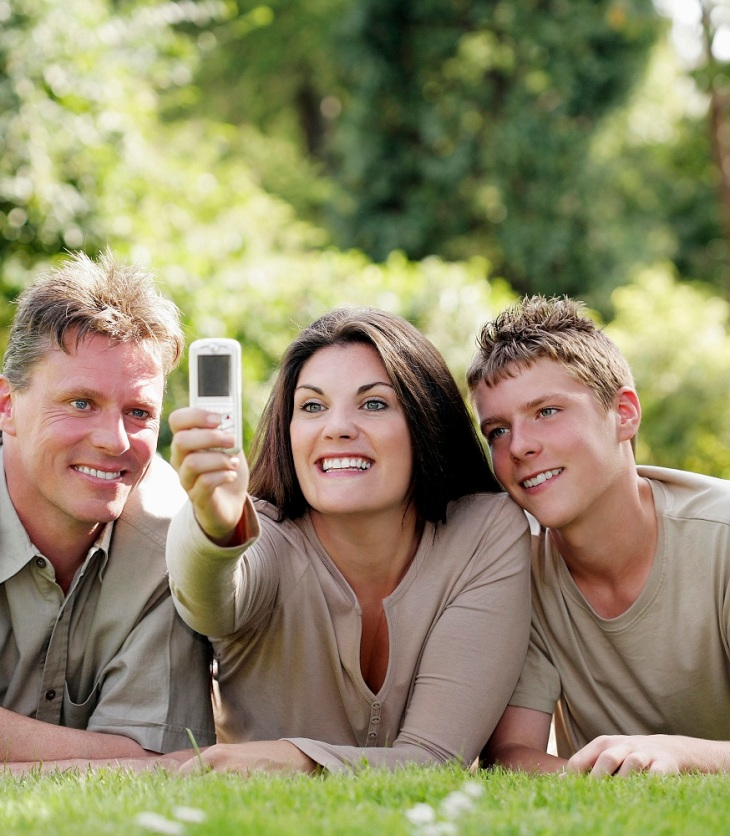 mom taking a picture of her husband and son as they lay on the grass