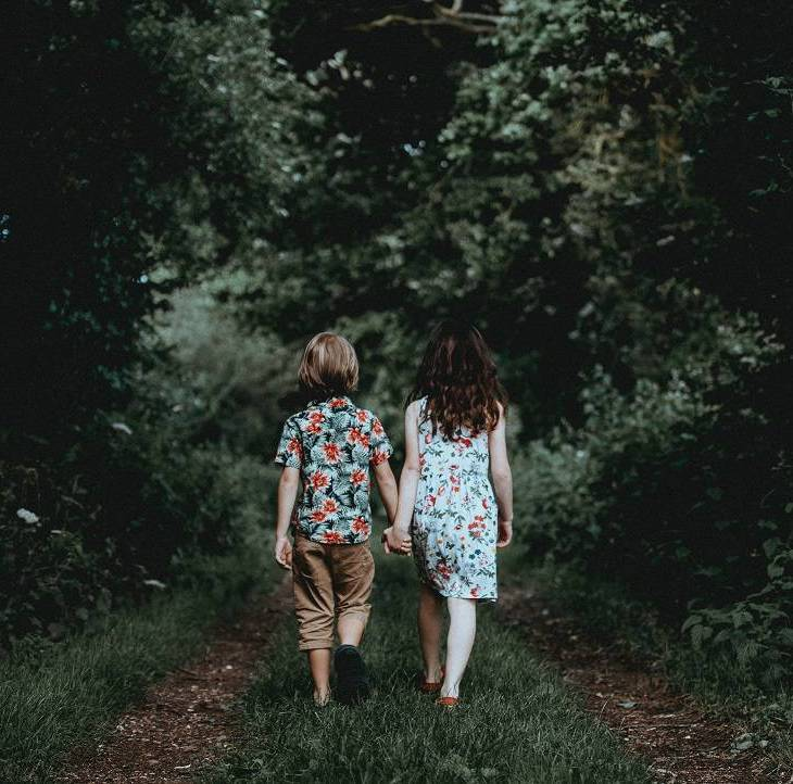 little boy and girl holding hands walking through the woods