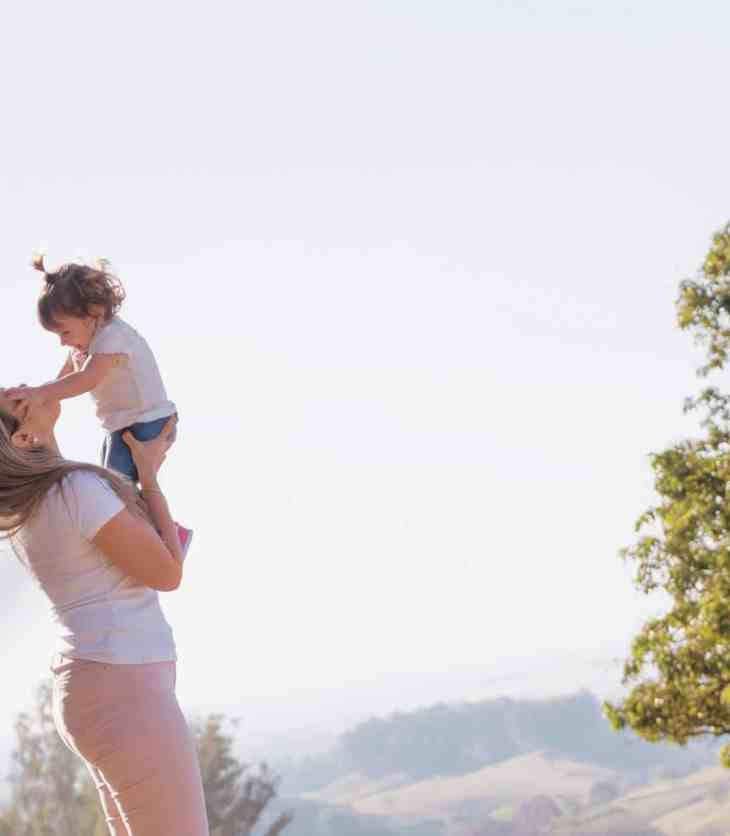 Mom talking to her little daughter and she is holding her in the air
