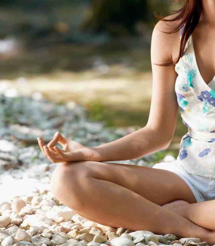 Arm and leg of Young woman meditating by forest river, cropped image