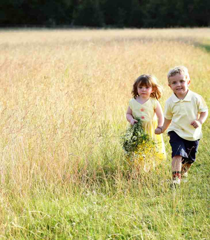 little girl holding a basket of flowers and holding hands with a little boy in a grassy field |lawnmower parenting