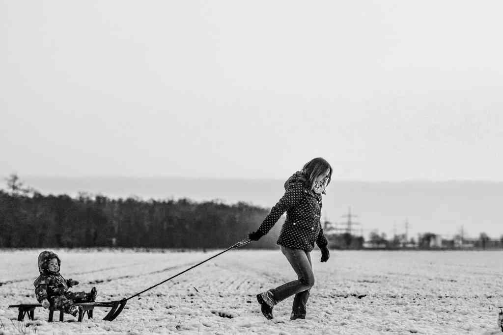 woman pulling child on sled
