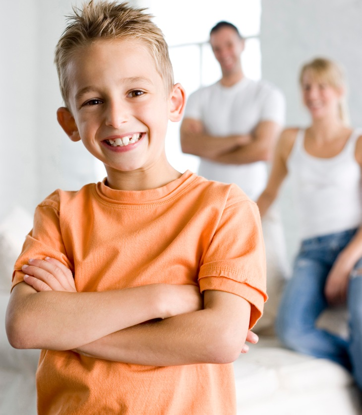 confident child standing in front of parents
